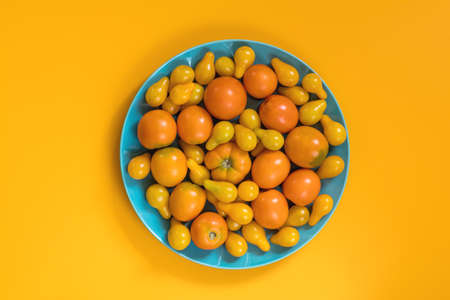 Many different yellow  tomatoes on yellow surface. Beautiful food art background, top view.