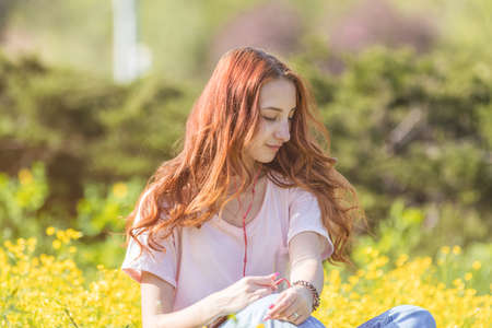Young girl teenager on a lawn field with yellow flowers. Long chestnut hair. Sunshine, springtime, blue sky. Coloring and processing photos with soft selective focus. Shallow depth of field. Stock Photo