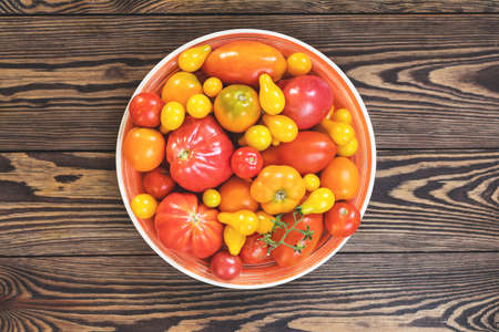 Many different red orange yellow tomatoes on dark wooden surface. Beautiful food art background, top view. Stock Photo