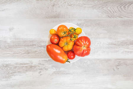 Many different red orange yellow tomatoes on light wooden surface. Beautiful food art background, top view. Stock Photo