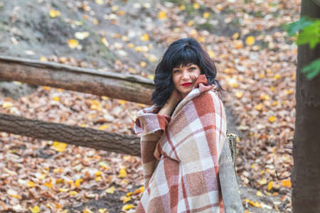 Cute happy beautiful sexy brunette female girl resting sitting in autumn garden on the steps, wrapped in a woolen plaid blanket. Stock Photo