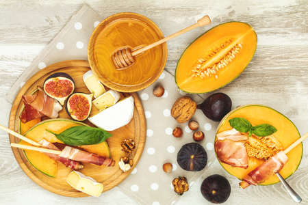 Cantaloupe melon sliced with Prosciutto jamon, basil leaves, fig, Camembert, honey and dried cherry. Italian appetizer on wooden background.