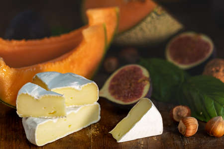 Cantaloupe melon sliced with Camembert, basil leaves, fig, and dried cherry. Italian appetizer on wooden background.