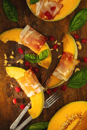 Cantaloupe melon sliced with Prosciutto jamon, basil leaves, fig and dried cherry. Italian appetizer on wooden background.