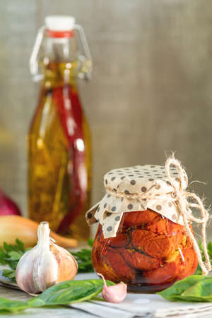 Sun dried tomatoes in glass jar, onion, basil leaves and garlic on cutting board, on wooden background Stock Photo