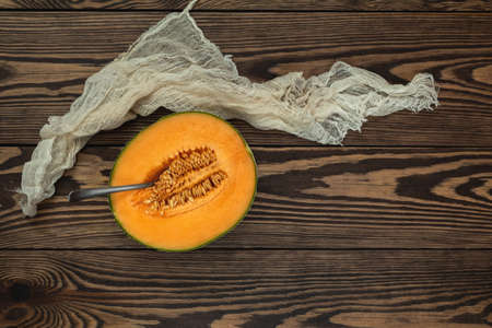 Organic cantaloupe melon slices siting on wooden cutting board with seeds. Top view, copy space, wooden background.
