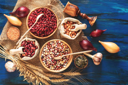 Assortment of kidney bean - mung bean, red kidney bean, white bean, brown bean, indian corn, pumpkin seeds, lentils, onions, garlic, wheat sprouts on dark blue wooden background Stock Photo - 109230221