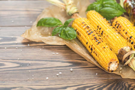 Corn baked in olive oil, with salt and basil on parchment paper on a dark surface Stock Photo - 109230222