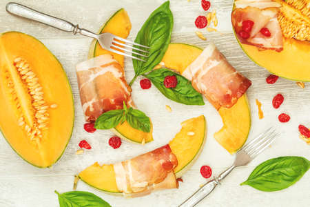 Cantaloupe melon sliced with Prosciutto jamon, basil leaves, fig and dried cherry. Italian appetizer on wooden background Stock Photo - 109230223
