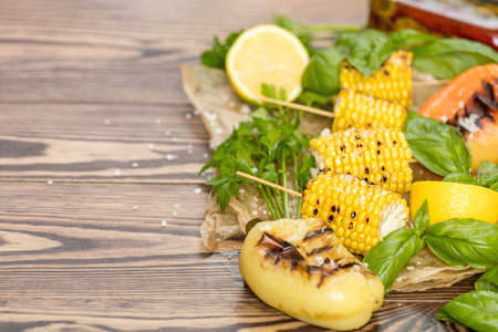 Corn baked in olive oil, with pepper, salt and basil on blue dish on a black stone surface. Vegetarian, vegan menu Stock Photo - 109230224