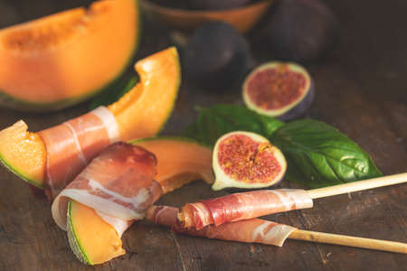 Cantaloupe melon sliced with Prosciutto jamon, basil leaves, fig and dried cherry. Italian appetizer on wooden background. Stock Photo - 109230225