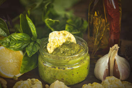 Fresh homemade pesto sauce close up and food ingredients for making pesto. Shallow depth of the field, toned and processing photo Stock Photo - 109230227