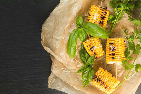 Corn baked in olive oil, with salt and basil on parchment paper on a dark surface Stock Photo - 109230229