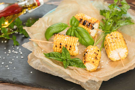 Corn baked in olive oil, with salt and basil on parchment paper on a dark surface Stock Photo - 109230232