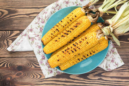 Corn baked in olive oil and salt on blue dish on dark surface. Tasty grilled corn cobs Stock Photo - 109230236