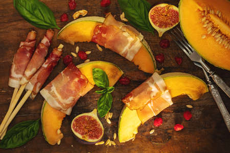 Cantaloupe melon sliced with Prosciutto jamon, basil leaves, fig and dried cherry. Italian appetizer on wooden background. Stock Photo - 109230238