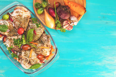 Raw fresh chicken thighs with spices and vegetables in a glass bowl. Many food ingredients on light blue wooden background. Top view, shallow depth of the field, toned and processing photo. Stock Photo - 109431921