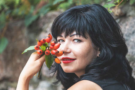 Red rose hips in womens hands. Sexy beautiful pretty brunette with red lipstick. Selective focus, shallow depth of the field. Stock Photo