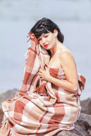 Cute happy beautiful sexy brunette female girl resting sitting on the stone near river, wrapped in a woolen plaid blanket. Stock Photo