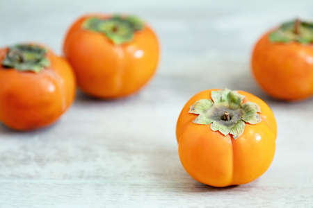 Autumn harvest Persimmon fruits in bowl on a wooden table background. Copy space. Light style. Natural remedy Stock Photo