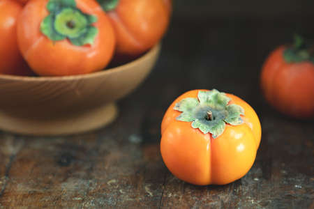 Autumn harvest Persimmon fruits in bowl on a wooden table background. Copy space. Dark rustic style. Natural remedy
