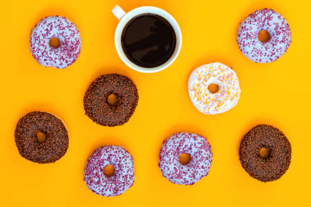 Delicious glazed donuts and cup of coffee on yellow surface. Flat lay minimalist food art background. Top view.