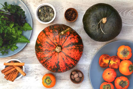 Green and orange Pumpkin, persimmons and ingredients for tasty vegetarian cooking on light wooden surface, food art background, top view. Stock Photo