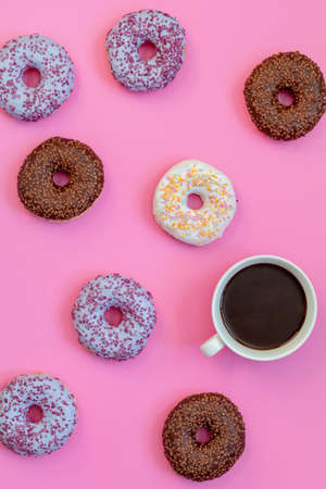 Delicious glazed donuts and cup of coffee on pink surface. Flat lay minimalist food art background. Top view. Stock Photo