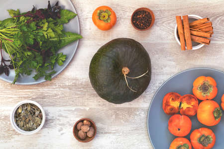 Green Pumpkin, persimmons and ingredients for tasty vegetarian cooking on light wooden surface, food art background, top view.
