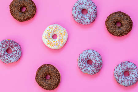 Delicious glazed donuts on pink surface. Flat lay minimalist food art background. Top view.