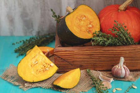 Green and orange Pumpkin,  ingredients for tasty vegetarian cooking on light wooden surface, food art background
