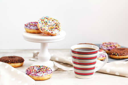 Delicious glazed donuts and cup of coffee on light wooden background. Beautiful romantic breakfast or lunch concept. Shallow depth of the field.