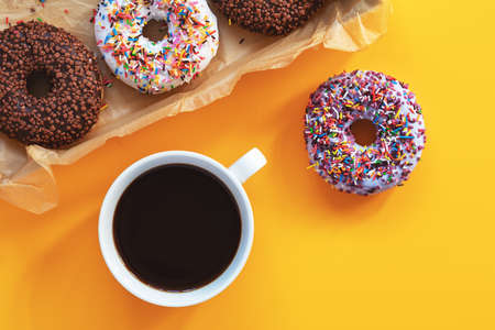 Delicious glazed donuts in box and cup of coffee on yellow surface. Flat lay minimalist food art background. Top view.