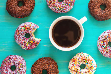 Delicious glazed donuts and cup of coffee on turquoise surface. Flat lay minimalist food art background. Top view.