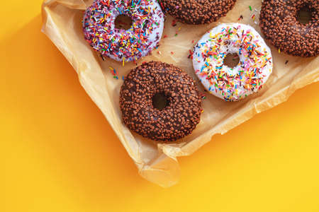 Delicious glazed donuts in box on yellow surface. Flat lay minimalist food art background. Top view. Stock Photo