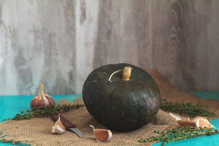 Green Pumpkin, ingredients for tasty vegetarian cooking on light wooden surface, food art background
