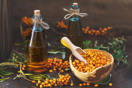 Natural, organic sea-buckthorn berry in bowl and sea buckthorn oil in glass vintage bottle on dark wooden background. Dark rustic style, natural remedy. Stock Photo