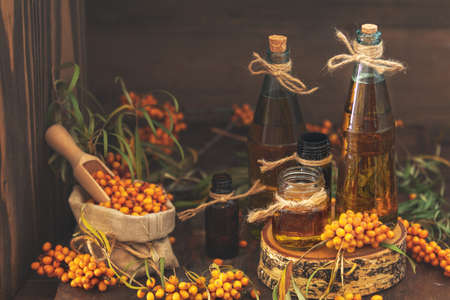 Natural, organic sea-buckthorn berry in linen bag and sea buckthorn oil in glass vintage bottles on dark wooden background. Dark rustic style, natural remedy.