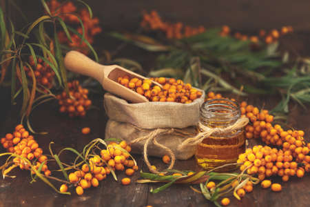 Natural, organic sea-buckthorn berry in linen bag and sea buckthorn oil in glass vintage bottle on dark wooden background. Dark rustic style, natural remedy.