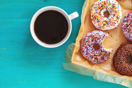 Delicious glazed donuts in box and cup of coffee on turquoise blue surface. Flat lay minimalist food art background. Top view.