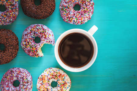 Delicious glazed donuts and cup of coffee on turquoise blue surface. Flat lay minimalist food art background. Top view.