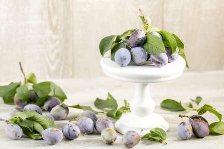 Many juicy beautiful amazing nice plums on light wooden background. Beautiful food art background