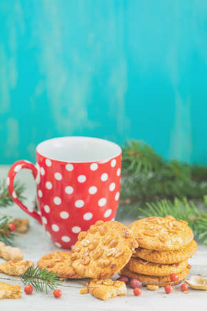 Christmas and New Year composition with delicious peanut cookies, peanuts and cup of coffee or tea, spruce branches and pine cones on light table and blue background. Stock Photo