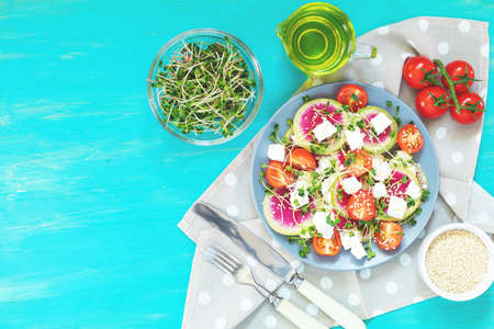 Healthy delicious tasty salad with tomatoes, radishes, cheeses, sprouts and sesame in plate on turquoise wooden background, top view,  .