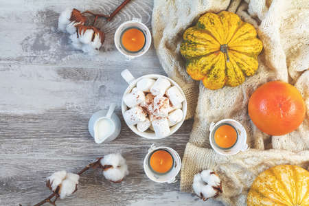 Top view composition with cup of coffee and marshmallow, pumpkin, grapefruit, cotton plant flower branches, candles and copy space. Autumn winter beautiful background, cozy home concept