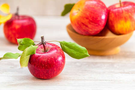 Autumn harvest red apples fruits on a light gray wooden table background. Copy space. Natural remedy. Shallow depth of the field.
