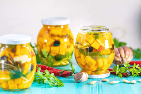 Marinated preserving jars. Homemade orange cut pumpkin pickles with red hot chili peppers, fresh parsley, spices on light turquoise wooden background. Fermented food.