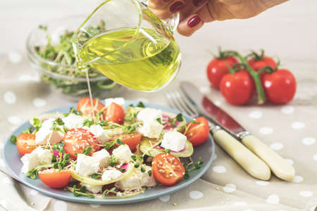 Healthy delicious tasty salad with tomatoes, radishes, cheeses, sprouts and sesame in plate on light wooden table dressed with olive oil, shallow depth of the field