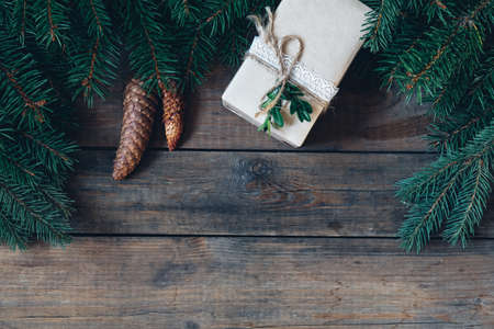 Christmas table place setting. Holidays background. Christmas gift and spruce branch with cones on dark wooden surface.