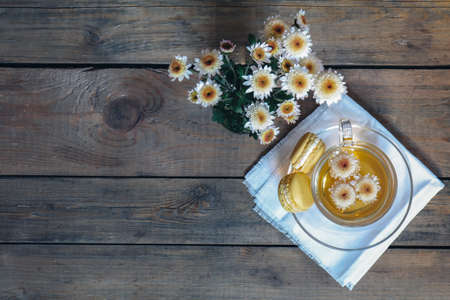 Cup of tea with chrysanthemum flowers and macaroons on the dark wooden surface, top view, copy space, cinematic color.